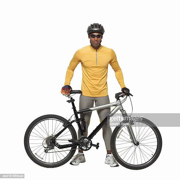 portrait of a man wearing cycling gear holding a bicycle