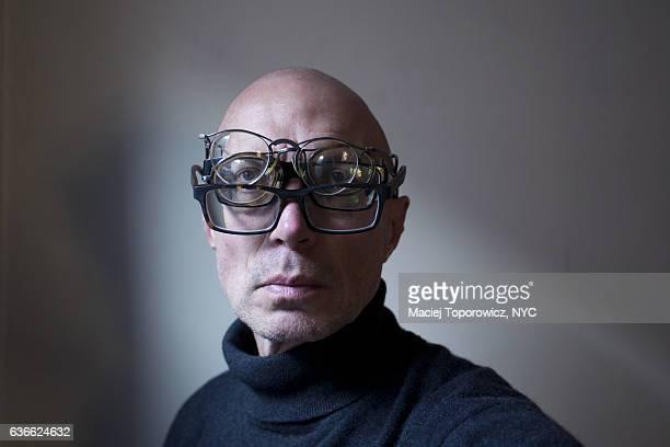 Portrait of a man wearing multiple eyeglasses.