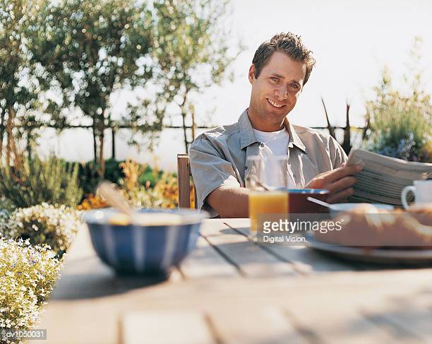 Portrait of a Man With a Newspaper Having Breakfast in His Garden in the Summer
