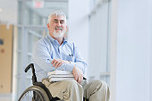 Portrait of a man with books sitting in a wheelchair
