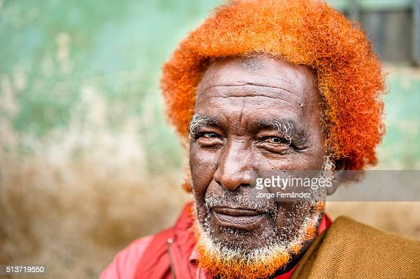 Portrait of a man with curly hair and beard dyed to red color