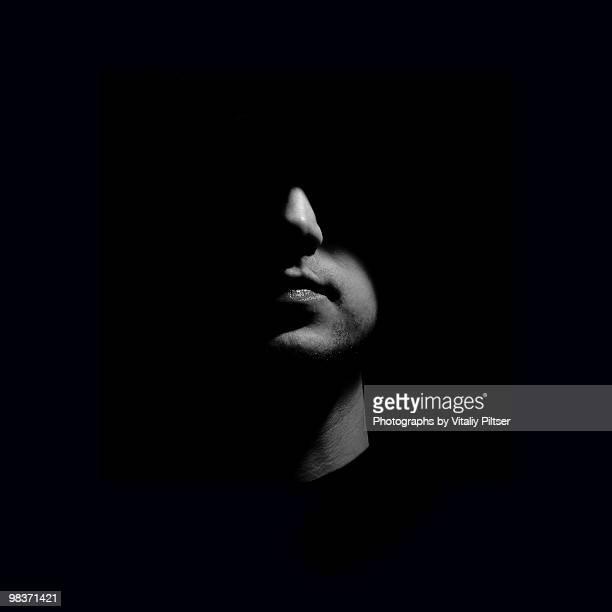 Portrait of a man with face half lit.