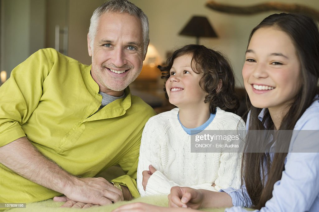 Portrait of a man with his children smiling : Stock Photo