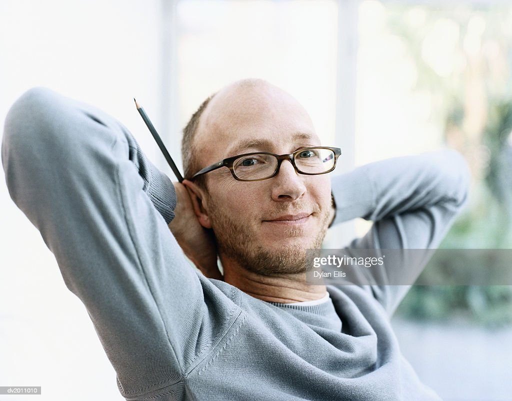 Portrait of a Man With His Hands Behind His Head, Holding a Pencil : Stock Photo