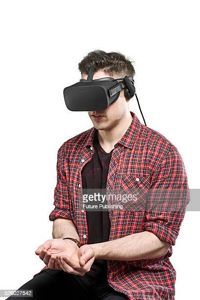 Portrait of a man with his hands cupped together while wearing an Oculus Rift virtual reality headset taken on April 13 2016