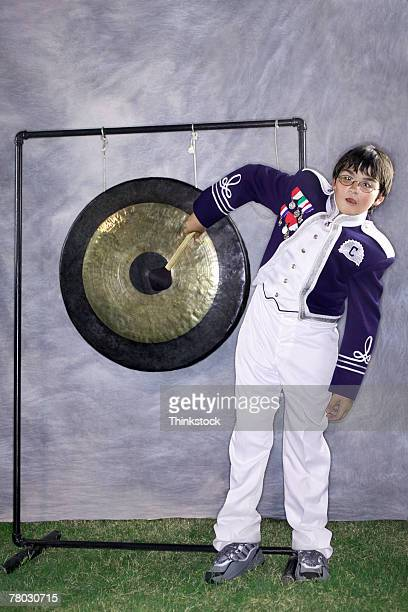 Portrait of a marching band member hitting a large gong.