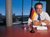 Portrait of a Mature Businessman Sitting at a Conference Table by a German Flag