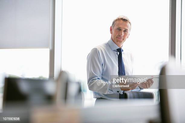 Portrait of a mature businessman with document at office