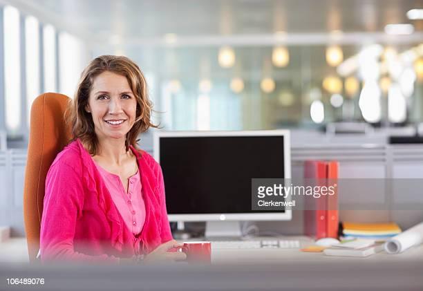 Porträt von Reife Geschäftsfrau mit Kaffeetasse auf Schreibtisch