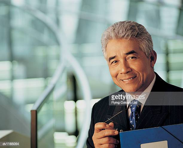 Portrait of a Mature CEO Holding Spectacles and a Folder