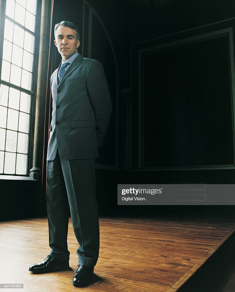 Portrait of a Mature CEO Standing in His Home With His Hands Behind His Back