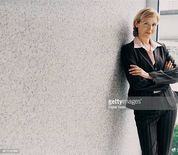 Portrait of a Mature CEO With Her Arms Crossed Leaning Against a Wall