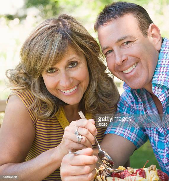 Portrait of a mature couple eating fruit salad and smiling