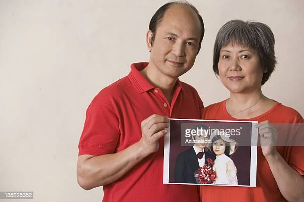 Portrait of a mature couple holding a wedding photograph