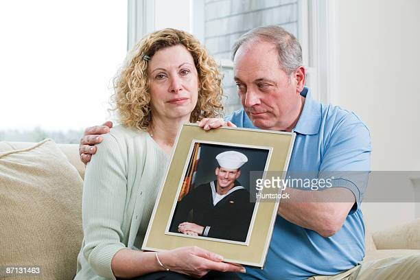 Portrait of a mature couple holding picture of their son working in the military