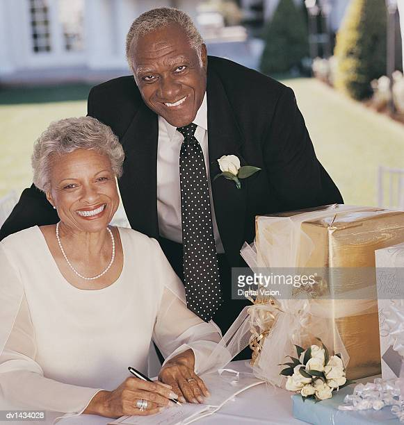 Portrait of a Mature Couple Signing a Wedding Book on a Table With Gifts