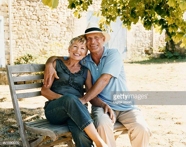 Portrait of a Mature Couple Sitting Side By Side on a Garden Bench