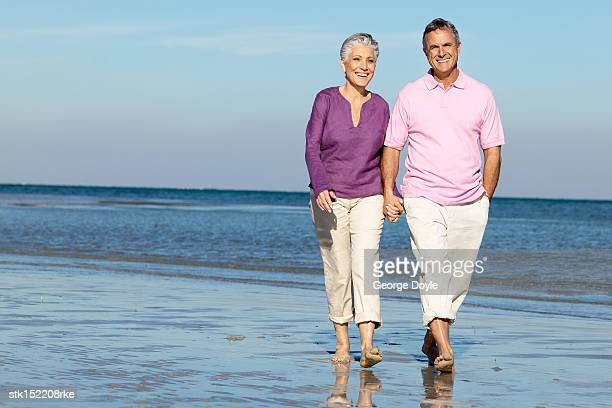 portrait of a mature couple walking hand in hand on the beach