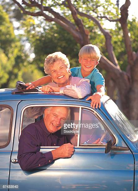 portrait of a mature couple with grandson sitting in a car