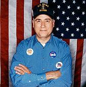 Portrait of a Mature Male Veteran Standing in Front of a Stars and Stripes Flag Wearing Election Badges