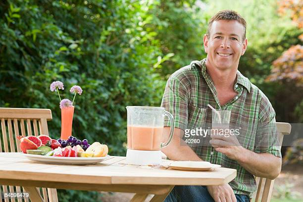 Portrait of a mature man holding a glass of juice and smiling
