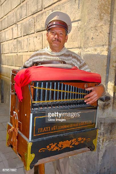 Portrait of a mature man holding a harmonipan, Mexico City, Mexico