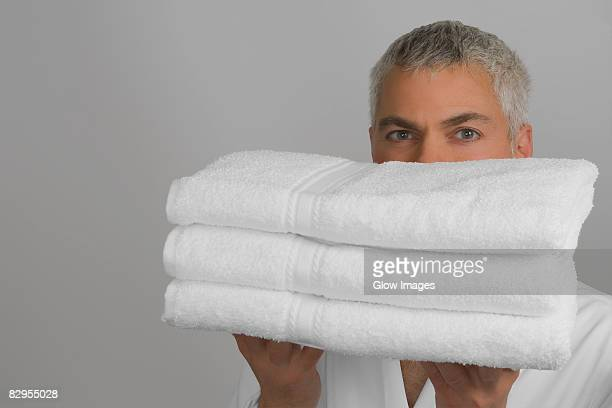 Portrait of a mature man holding a stack of folded towels