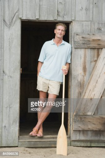 Portrait of a mature man leaning against the door of a beach hut : Foto de stock