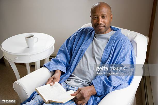 Portrait of a mature man sitting in an armchair and holding a book