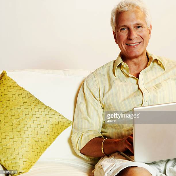 Portrait of a mature man sitting on a couch and using a laptop