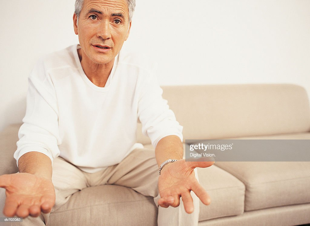 Portrait of a Mature Man Sitting on a Sofa with his Arms Stretched out : Stock Photo