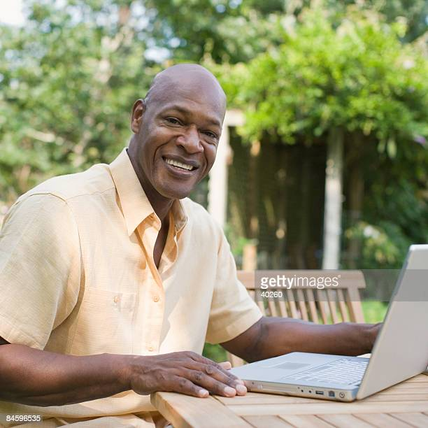 Portrait of a mature man using a laptop and smiling