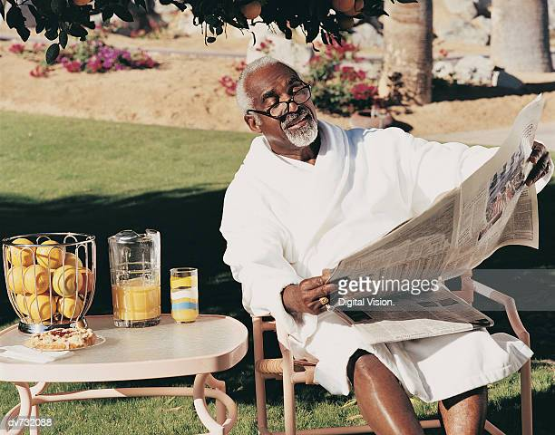 Portrait of a Mature Man Wearing a Dressing Gown and Reading a Newspaper in His Garden