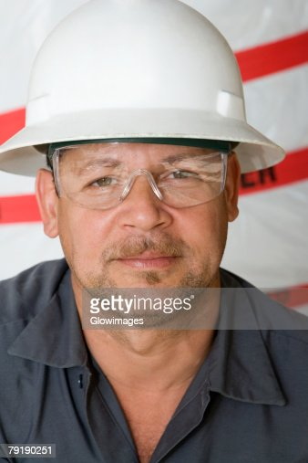 Portrait of a mature man with a pair of protective eyewear and a hardhat : Stock Photo
