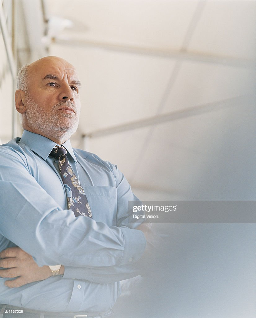 Portrait of a Mature, Serious CEO Standing With His Arms Crossed