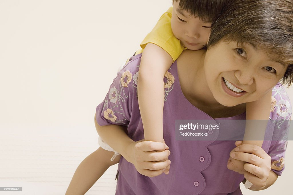 Portrait of a mature woman giving piggyback ride to her grandson : Stock Photo