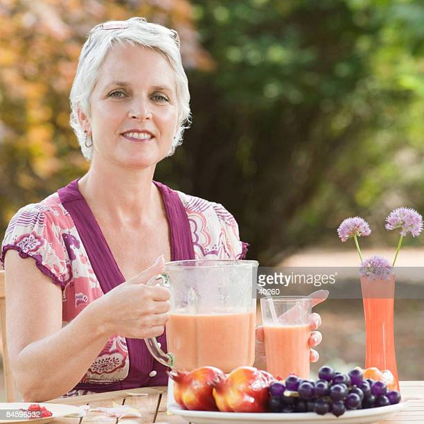 Portrait of a mature woman holding a blender filled with juice