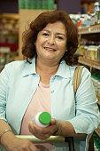 Portrait of a mature woman holding a bottle