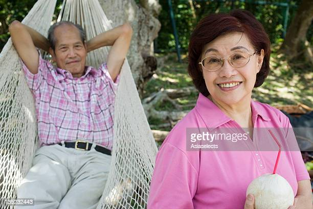 Portrait of a mature woman holding a coconut milk with her husband lying in a hammock behind her