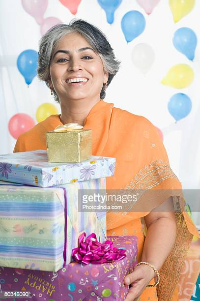 Portrait of a mature woman holding a stack of gifts