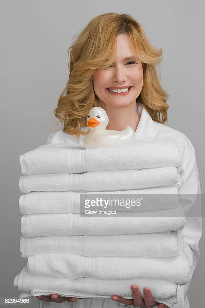 Portrait of a mature woman holding a stock of folded towels and smiling