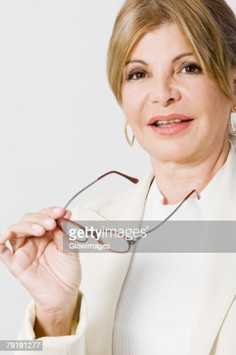 Portrait of a mature woman holding eyeglasses : Foto de stock