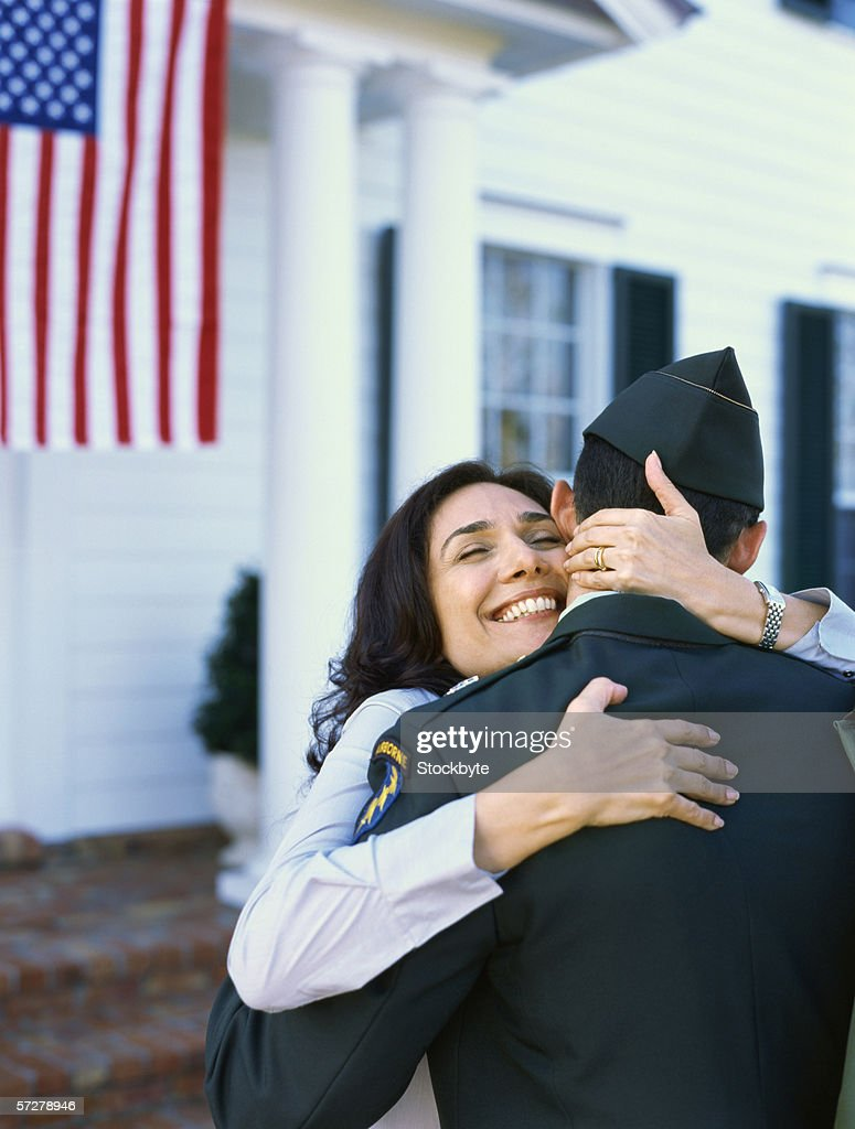 Portrait of a mature woman hugging a man in military uniform