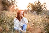 Beautiful woman sitting in the field enjoying the sunset