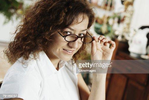 Portrait of a mature woman peeking over her eyeglasses : Stock Photo