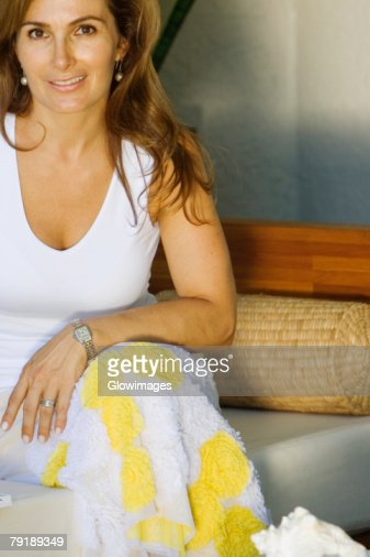 Portrait of a mature woman sitting on a couch and smiling : Foto de stock