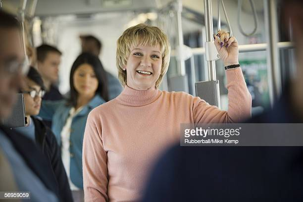 Portrait of a mature woman standing in a passenger train