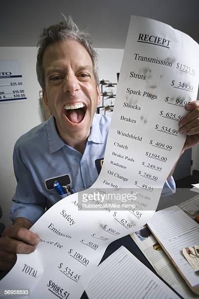 Portrait of a mechanic holding a bill