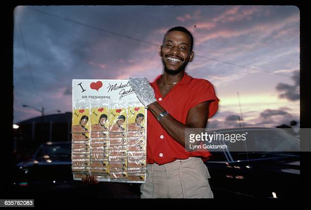 Portrait of a Michael Jackson fan selling 'I Love Michael' air fresheners in the parking lot of a concert venue Photograph 1984