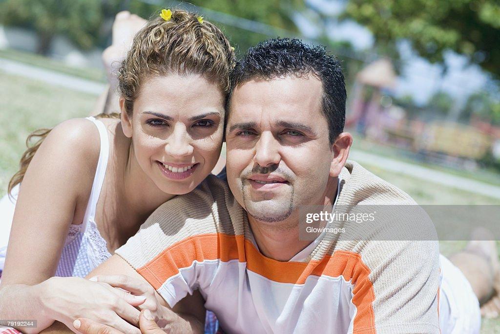 Portrait of a mid adult couple lying in a lawn : Foto de stock
